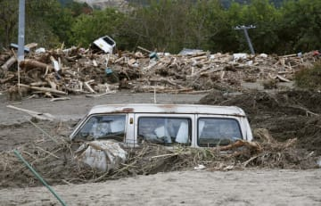 台風19号の影響による大雨で押し流され、泥に埋まったまま残された車=21日午後、宮城県丸森町