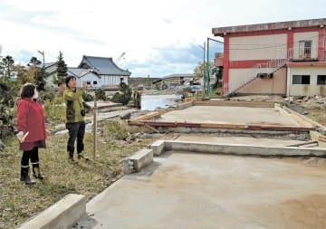 倉庫が流されたという現場で調査する佐藤准教授(右)=20日午前11時30分ごろ、宮城県大郷町粕川