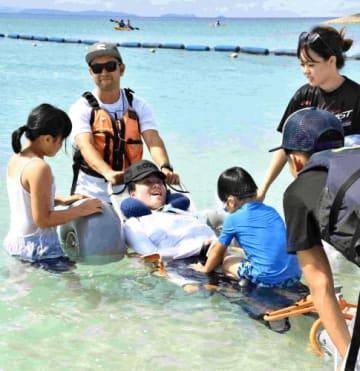子どもたちと一緒に海水浴を楽しむ浦崎綾乃さん=22日、豊見城市の豊崎美らSUNビーチ