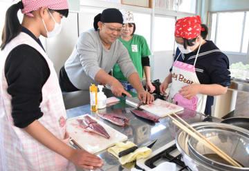 田上さん夫婦(中央)の指導の下、サバをさばいていく飫肥中生徒たち